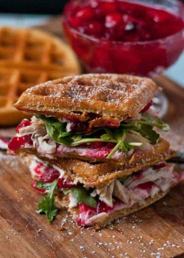 Two quartered waffle cranberry cream cheese turkey sandwiches stacked on a wood platform.