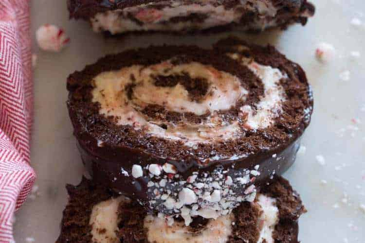 Overhead view of a Chocolate Peppermint Cake Roll with two slices overlapping each other, next to a red dish towel.