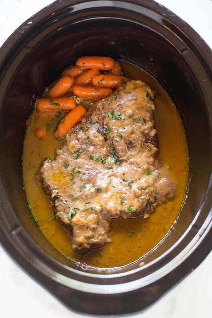 Overhead photo of a slow cooker with a cooked pot roast in gravy with carrotts