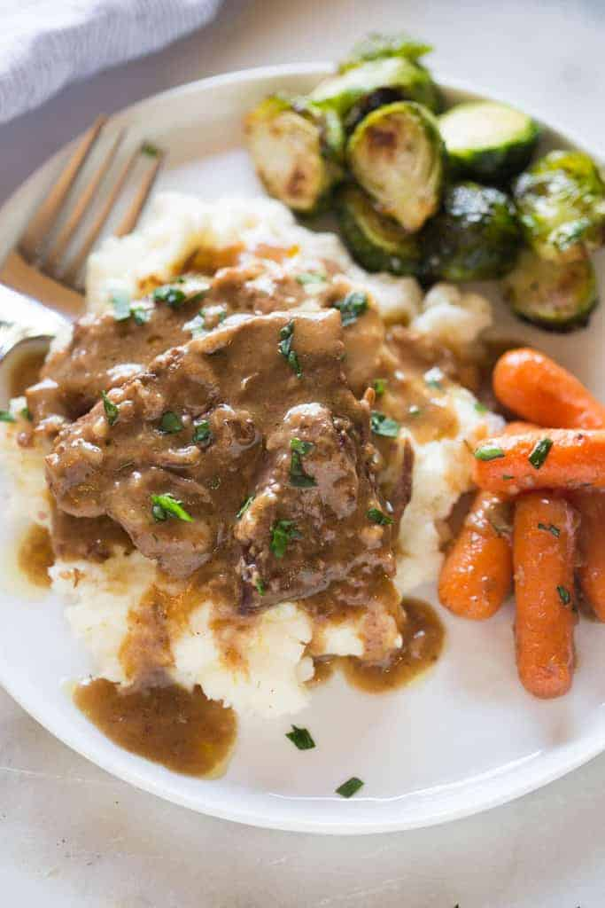 A plate filled with slow cooker pot roast served on top of cream mashed potatoes, with a side of cooked carrots and Brussels sprouts.