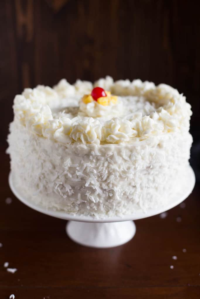 A white cake platter with a Coconut Cake on it, decorated with cream cheese frosting, sprinkled with coconut, and topped with a maraschino cherry and fresh pineapple.