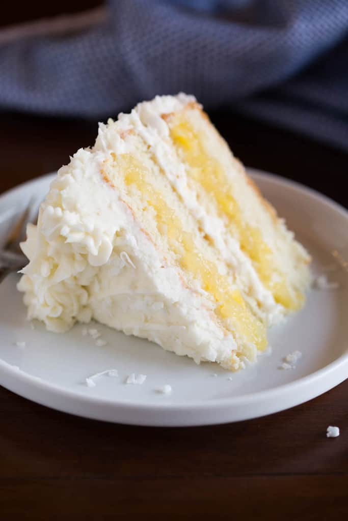 A slice of Coconut Cake with pineapple filling, laying on a white plate.