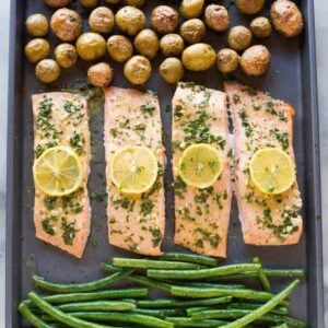 One pan baked salmon and vegetables on a large sheet pan with small red and yellow potatoes and green beans.