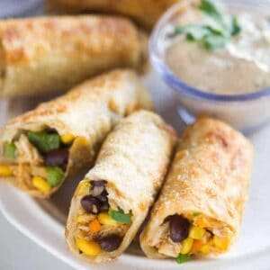 Southwest egg rolls on a plate with creamy cilantro dipping sauce.