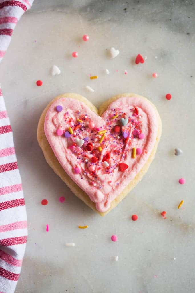 Heart shaped sugar cookie with pink frosting and sprinkles.