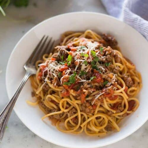 A pasta bowl full of Spaghetti made from the instant pot, garnished with parsley and parmesan.