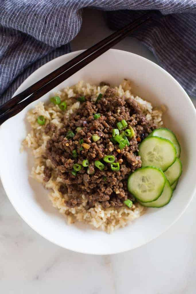 Korean ground beef garnished with green onion and served over brown rice, with a side of fresh sliced cucumbers.