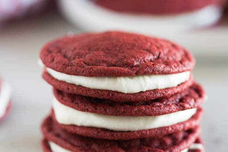 A stack of red velvet cookies with cream cheese filling.
