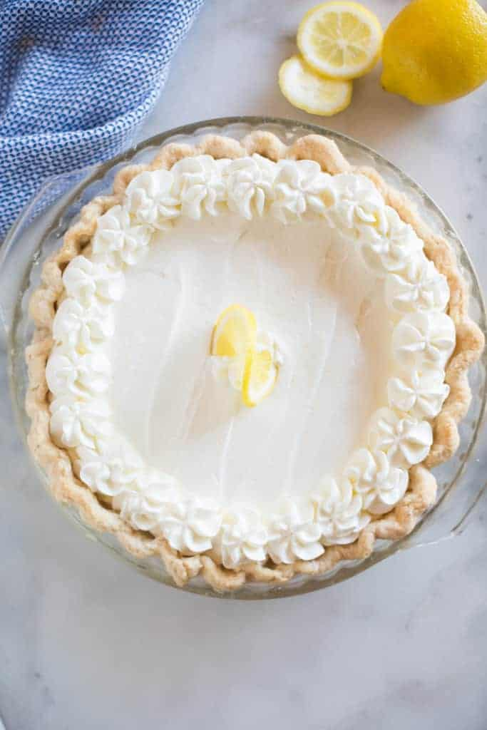 Overhead photo of a Lemon Sour Cream Pie with whipped cream topping and sliced lemons in the background.