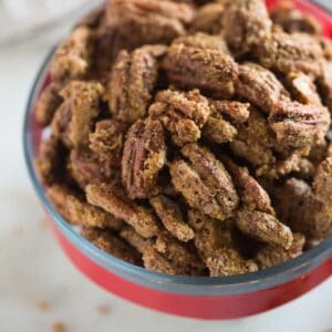 Candied pecans in a glass bowl with a red ribbon.