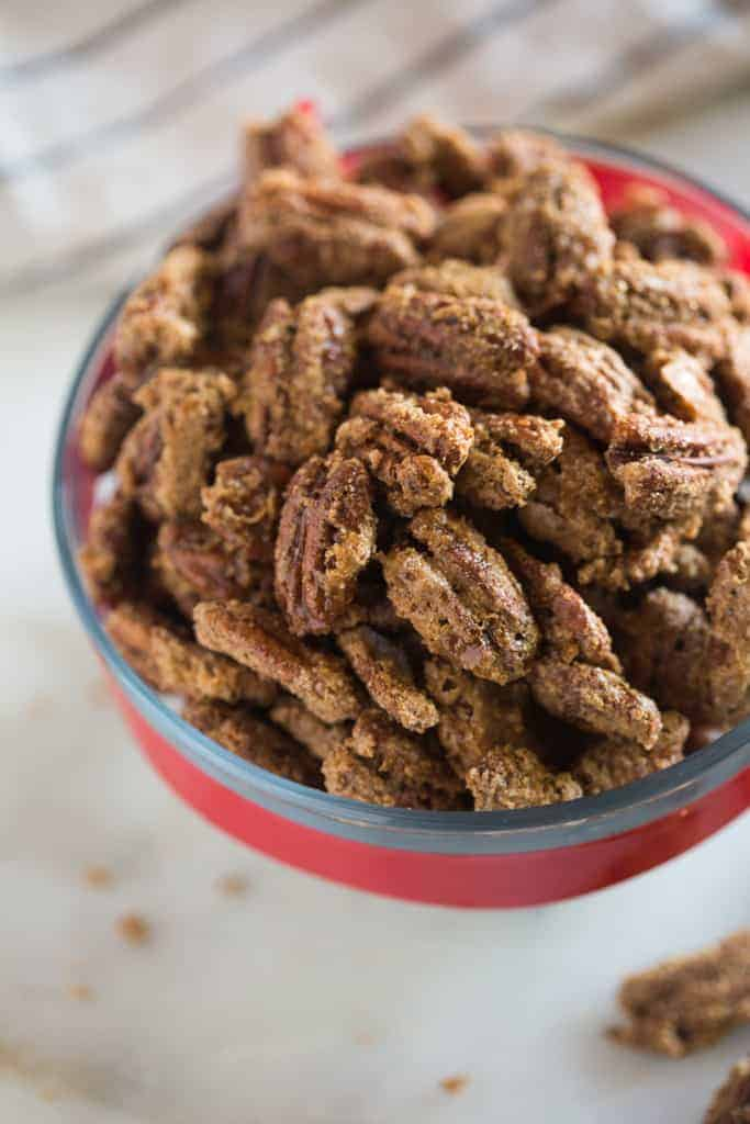 Candied pecans in a glass bowl with a red ribbon around it.
