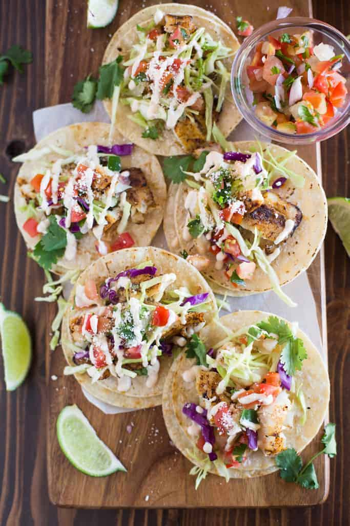 Overhead photo of fish tacos served on a wood board, on corn tortillas with toppings including cabbage and pico de gallo.