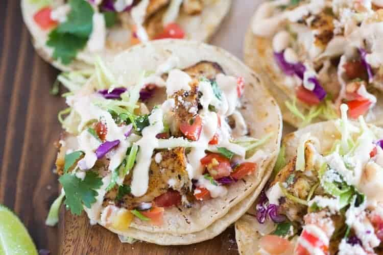 Fish tacos served on white corn tortillas and piled with toppings including cabbage, cilantro, pico de gallo and a white sauce