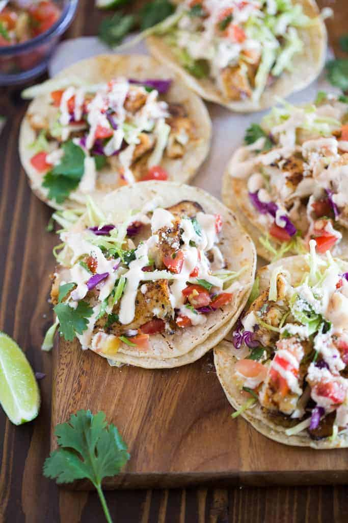Fish Tacos Served On White Corn Tortillas And Piled With Toppings Including Cabbage Cilantro