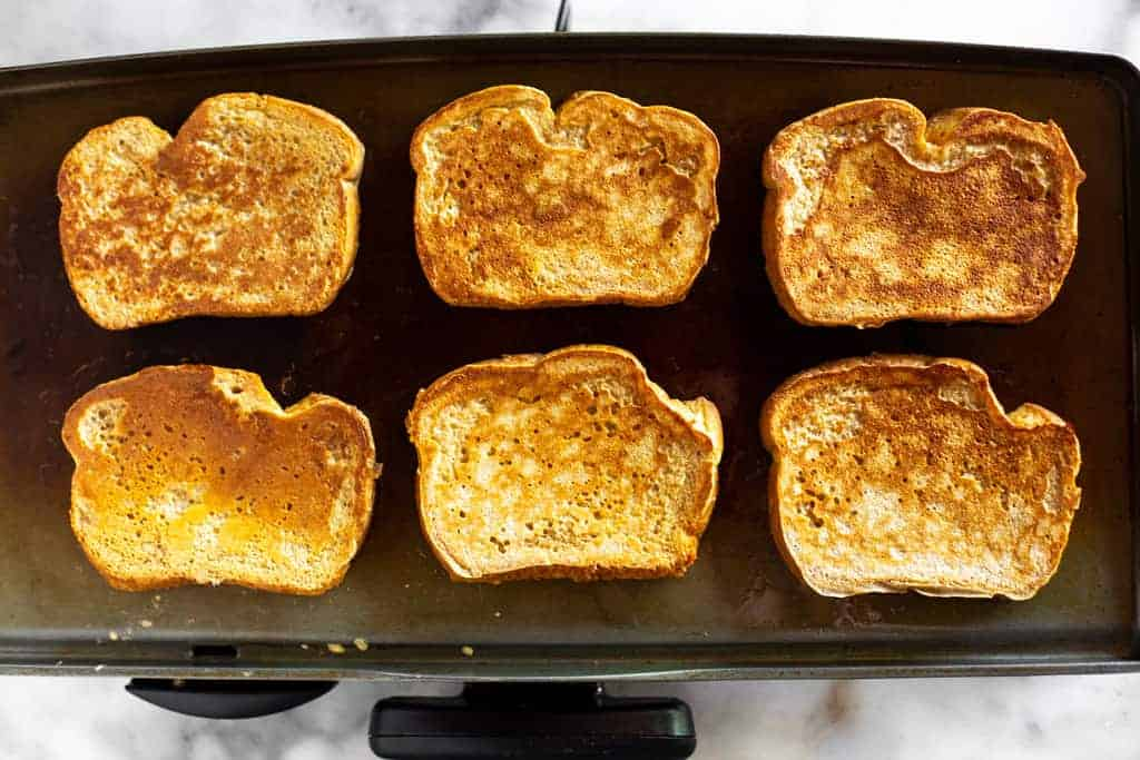 Six slices of French Toast cooking on a hot electric griddle.