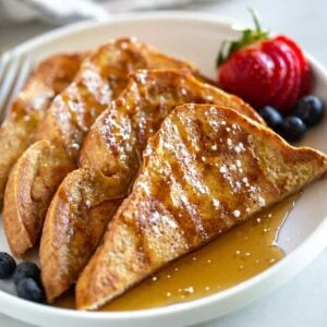 Four pieces of halved French Toast served on a plate, with powdered sugar and syrup on top.