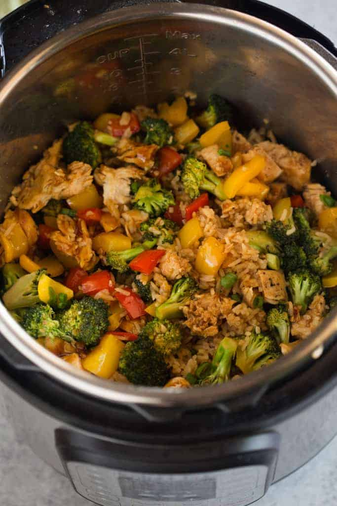 An instant pot filled cooked rice, vegetables, chicken and teriyaki sauce.