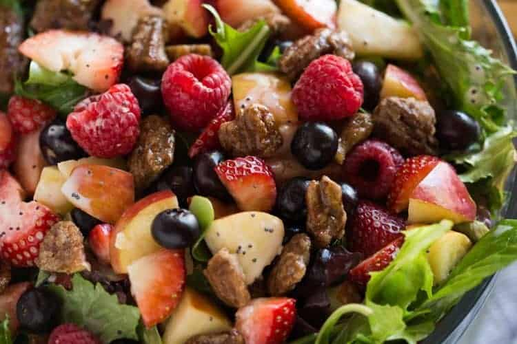 Mixed green salad with strawberries, blueberries, raspberries, apple, onion, feta cheese and poppyseed dressing in a glass bowl with salad tongs in the background.