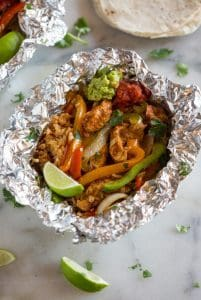 An opened foil packet dinner with chicken, rice, bell peppers, onion, lime and cilantro, with flour tortillas in the background.