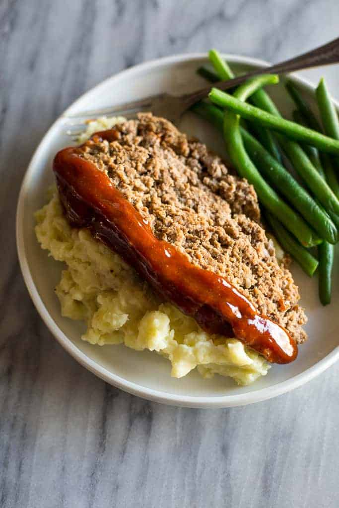 A white plate with mashed potatoes and a slice of meatloaf that were made in the instant pot and a side of green beans.