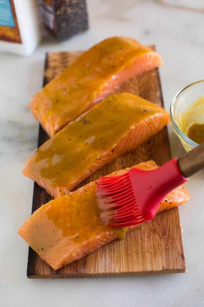 Raw salmon filets on a cedar plank board being spread with a brown sugar and mustard glaze.