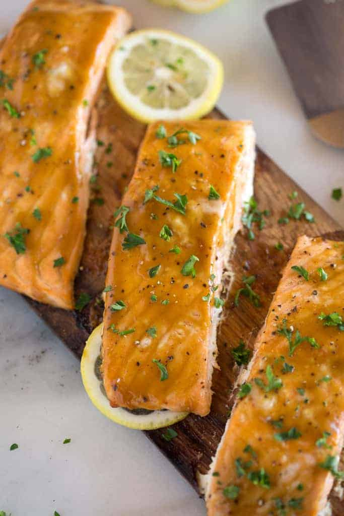 Cooked salmon filets on a cedar plank hot off the grill, served with sliced lemons.