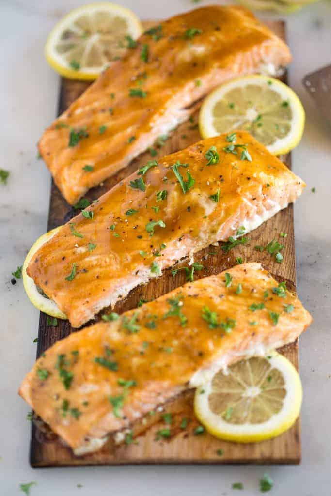 Salmon filets grilled on a cedar plank, topped with brown sugar and mustard glaze and served with sliced lemon.