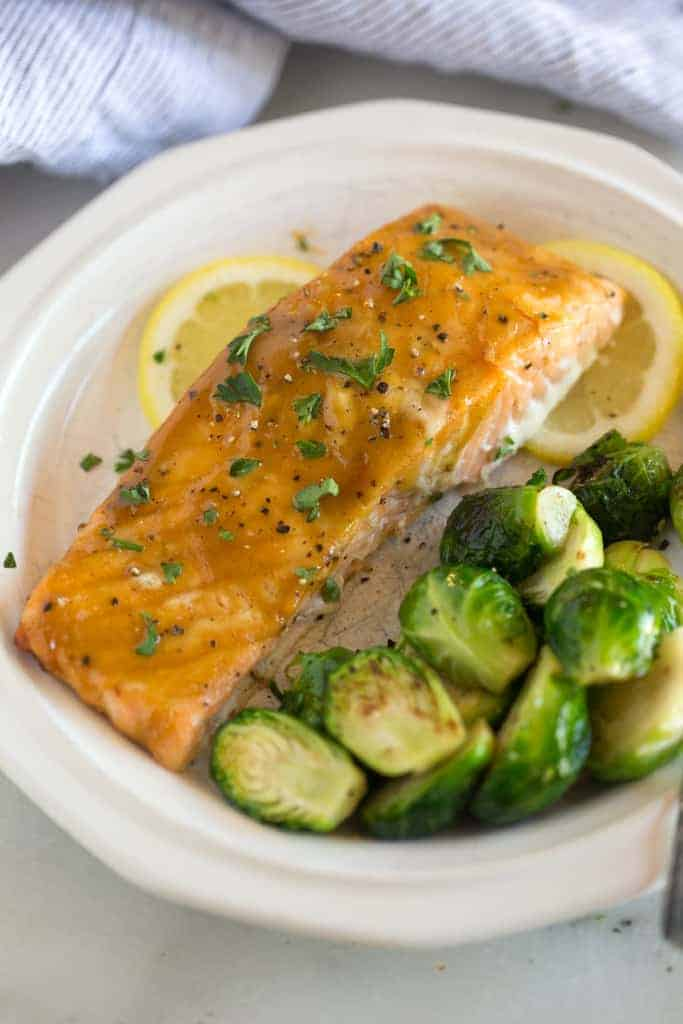 A white plate with salmon filet glazed with brown sugar and mustard, served with brussels sprouts.