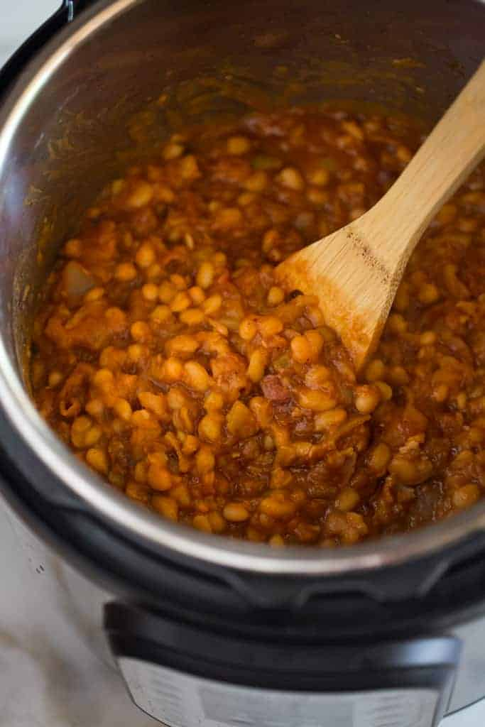 Baked beans cooked in an instant pot pressure cooker with a wooden spoon stirring the mixture.