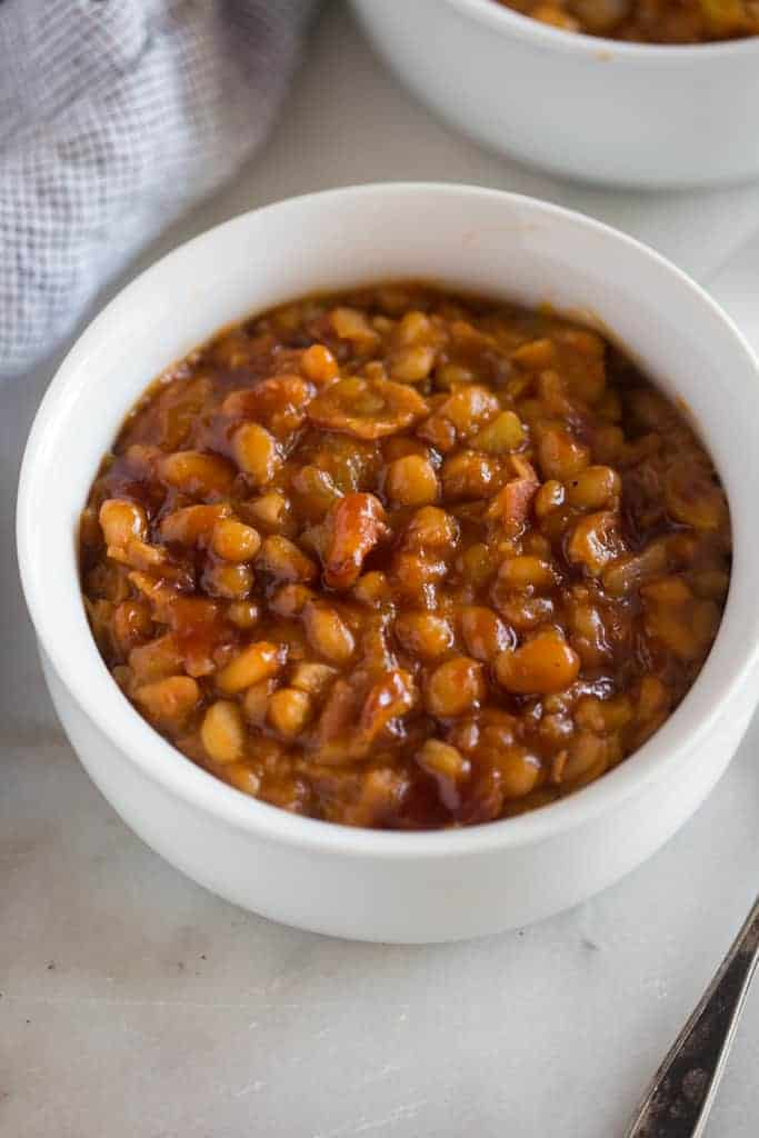 A close-up photo of a white bowl filled with baked beans with bacon, that were made in the instant pot.