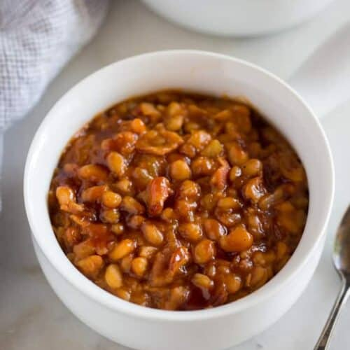 Instant Pot Baked Beans served in a white bowl with a handle, and another filled bowl in the background.
