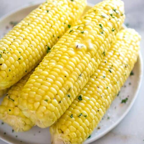 Perfect cooked ears of corn on the cob garnished with butter, salt and pepper and stacked on a white plate