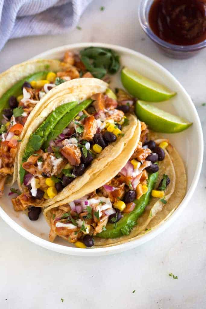 Grilled BBQ Chicken Tacos topped with corn, black beans, avocado, onion and tomatoes, served on a white plate with a small container of extra bbq sauce in the background