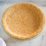 A homemade graham cracker crust baked in a clear pie pan, on a white marble board.