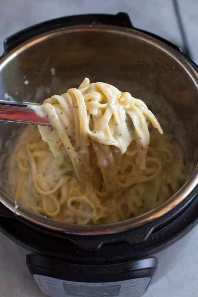 An instant pot filled with fettuccine alfredo with tongs lifting out a big spoonful of pasta to serve.