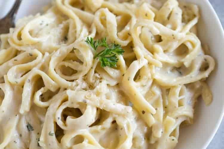 A white pasta bowl full of fettuccine alfredo with a piece of parsley on top for garnish, and a fork on the side.