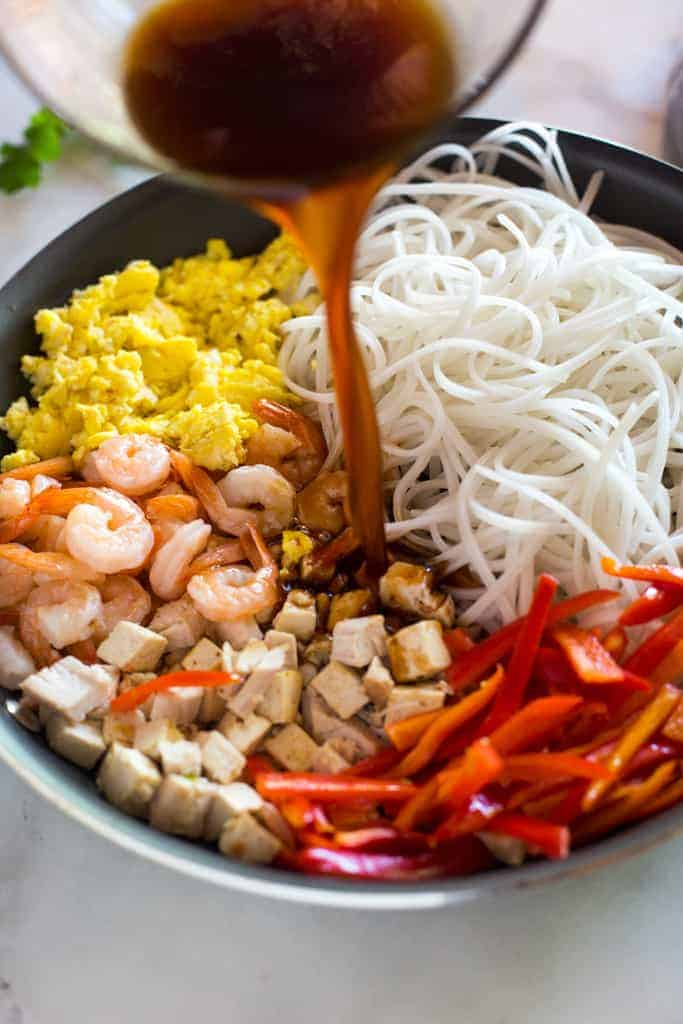 Pad thai sauce being poured over the other ingredients in pad thai, in a skillet, including rice noodles, shrimp, chicken, tofu, bell pepper and eggs.