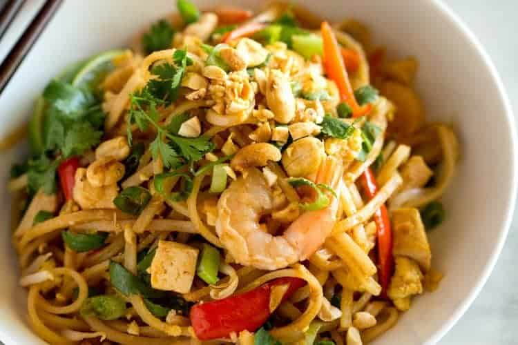 A white bowl filled with homemade pad thai including rice noodles, shrimo, cilantro and other toppings tossed in a pad thai sauce.