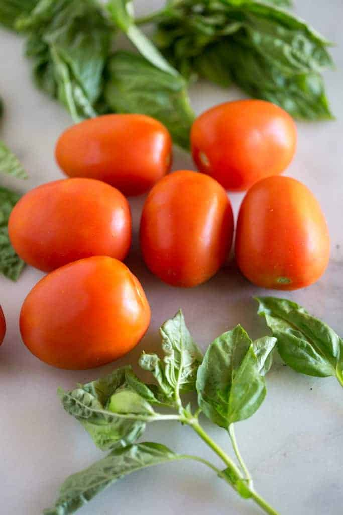Roma tomatoes on a white marble board with fresh basil leaves.