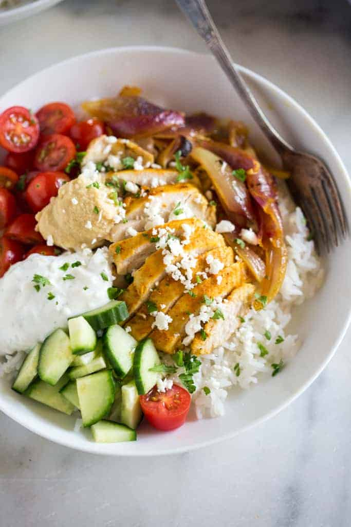 A white bowl filled with jasmine rice, chicken shawarma, cucumber, tomato, tzatziki sauce and hummus.