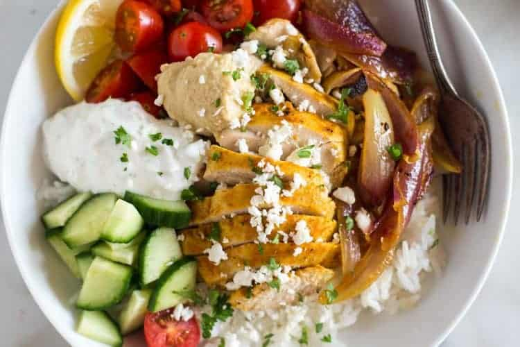 Chicken Shawarma bowls including a base of jasmine rice topped with marinated chicken, cucumber, tomato, red onion, hummus and tzatziki sauce.
