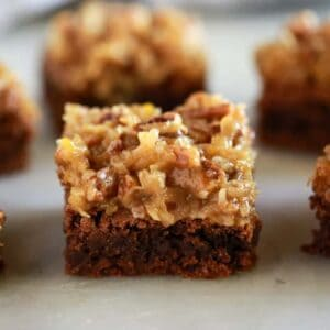 Cut German chocolate brownies served on a white board.