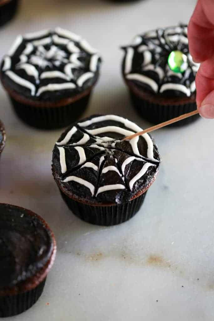 A cupcake frosted with black and white frosting and a toothpick pulling spiderweb lines into the frosting to make Halloween cupcakes with spiders.