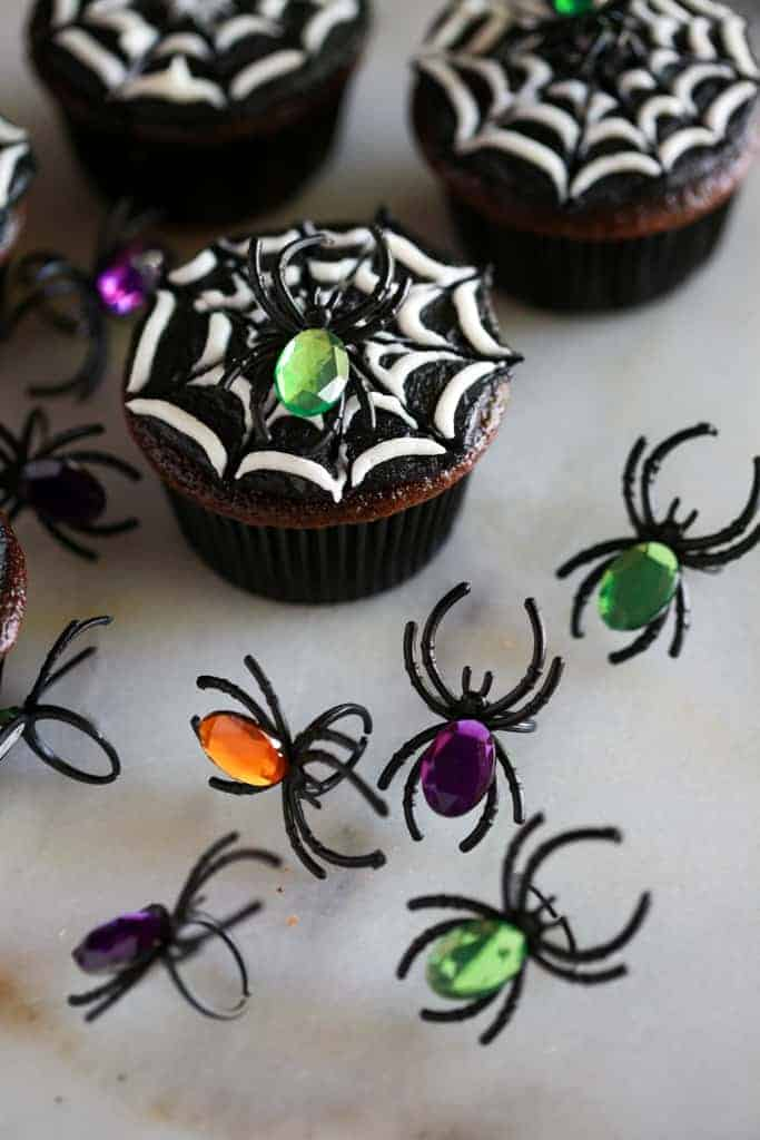 Toy spider rings with colored jewels on top used to decorate the halloween cupcakes in the background.