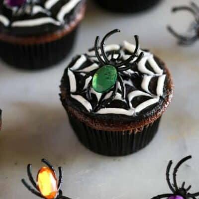 Halloween spider cookies made from a chocolate cupcake with black and white frosting to make a spider web, and a toy spider on top.