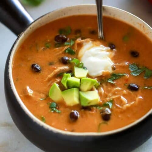 A bowl full of chicken enchilada soup that was made in the instant pot, topped with diced avocado, cilantro and a scoop of sour cream.