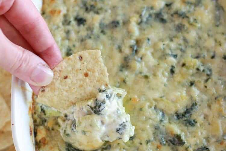 Spinach artichoke dip served in a white casserole dish with someone scooping some out with a chip.