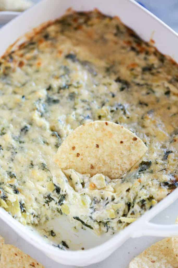Spinach Artichoke dip in a white square pan with a serving removed and a chip dipped in it.