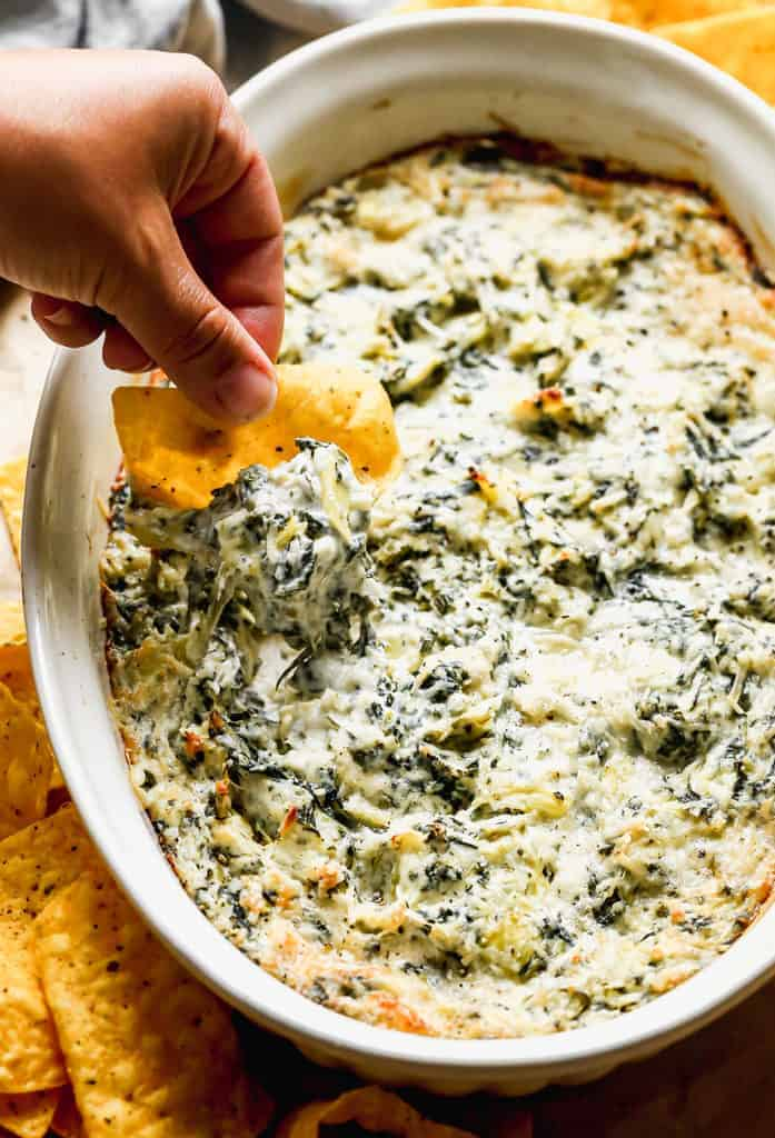 Spinach Artichoke Dip baked in pan, and a hand dipping a chip into it.