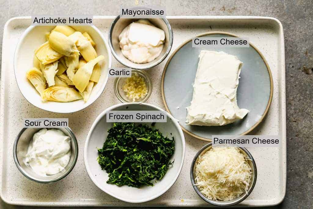 The ingredients needed to make Spinach Artichoke Dip labeled on a tray.